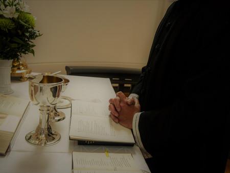 Billede af præst der beder ved alteret