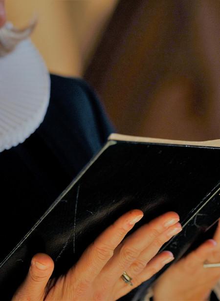 Billede af præst, der læser fra Bibelen